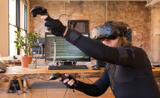 Man using a virtual reality HMD and handheld controllers with full-body motion capture